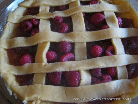Fresh raspberries peeking through the lattice of pastry before baking