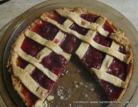 The cooked crostata, with a deep red hue created by the luscious raspberries