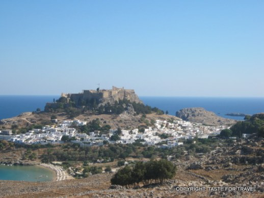 The blue and white town of Lindos scattered beneath the Crusader castle
